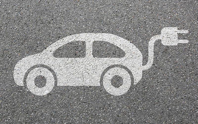 Vektorový obrázek bílého elektromobilu s kabelem a zástrčkou na šedém pískovém pozadí