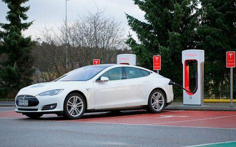 Elektromobil Tesla parkuje u nabíjecího stojanu a je připojen kabelem